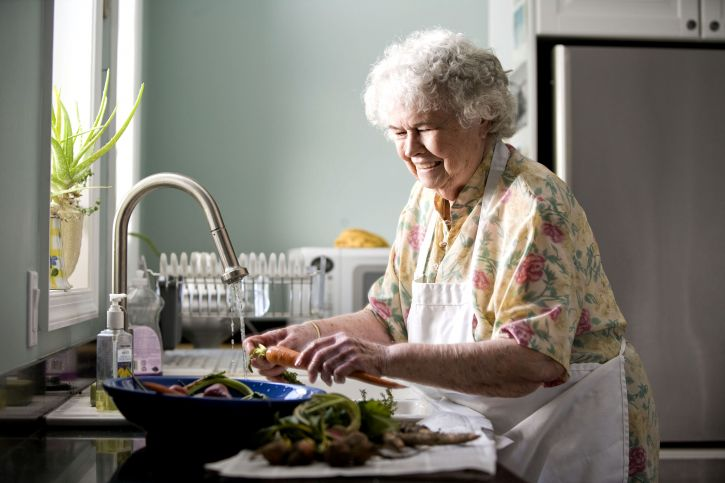 portrait of elderly woman in kitchen pictured while preparing a meal