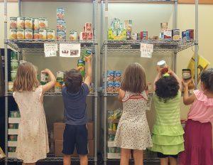 Adding Up Impact - Kids stock the KJFS Food Pantry